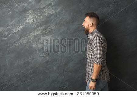 Man Cry Out In Despair And Shock. Expressing Strong Emotions, Anger At Grey Background, Studio Shot,