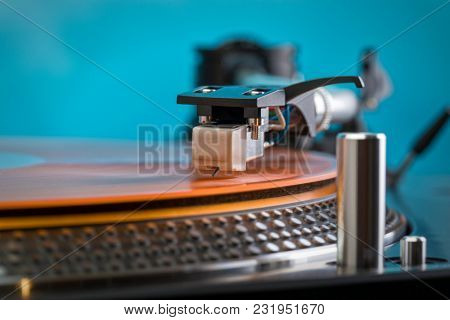 Closeup of turntable needle on orange colored vinyl record