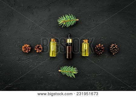 Pine Essential Oil In Bottles On Dark Background Top View Copy Space. Pattern With Pine Branch And C