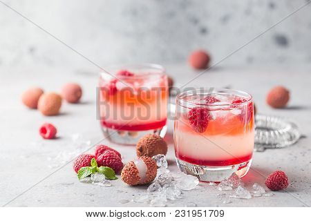 Refreshing Cold Lychee And Raspberry Cocktail In A Glasses With Ice And Berries Over Gray Background