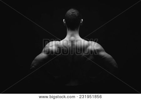 Unrecognizable Man Bodybuilder Shows Strong Hands And Back Muscles, Athletic Trapezius. Black And Wh