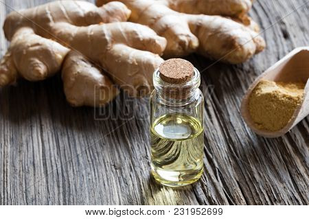 A Bottle Of Ginger Essential Oil With Ginger Root And Ground Ginger