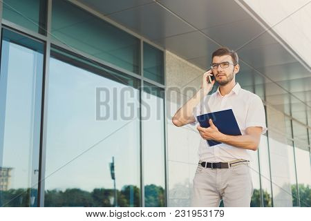 Attractive Pensive Businessman In Eyeglasses Is Holding Notepad And Talking On Mobile Phone While St