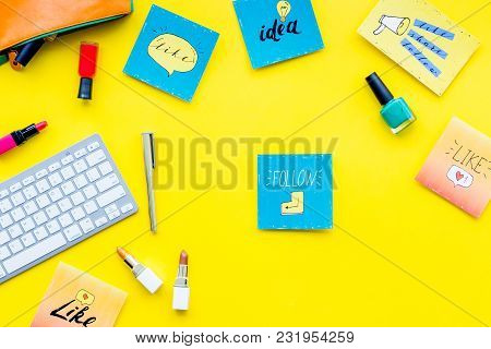 Female Blogger Concept. Work Desk With Keyboard, Cosmetics And Social Media Icons On Yellow Desk Top