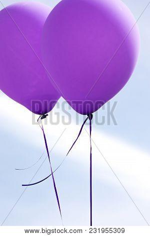 Two Purple Ballons Against Blue Sky Horizontal Photo