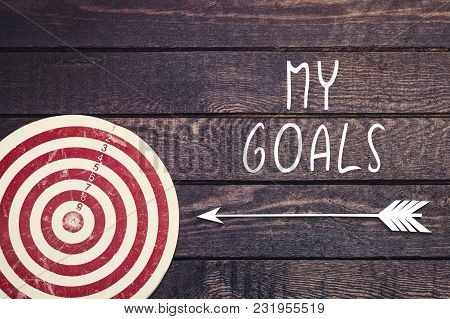 My Goals Inscription With Dart Board On Dark Wooden Wall.