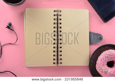 A Notebook On Springs With Brown Pages Rests On A Pink Background. Around The Notepad There Are Coff