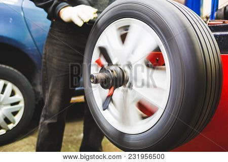 Mechanic Aligning Car Tire At Service