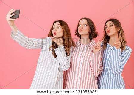 Three lovely young girls 20s wearing colorful striped pyjamas having fun and taking selfie using cell phone during happy sleepover isolated over pink background