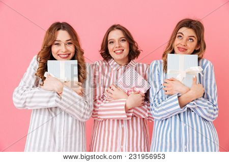 Photo of smiling girls friends 20s in home wear holding gift boxes and expressing excitement at slumber party isolated over pink background