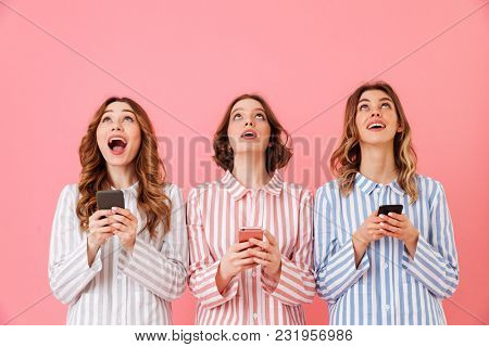 Three lovely young girls 20s wearing colorful striped pyjamas looking upward and using cell phones during happy sleepover isolated over pink background