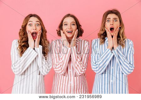 Portrait of three excited women 20s wearing colorful striped pajamas screaming in delight isolated over pink background