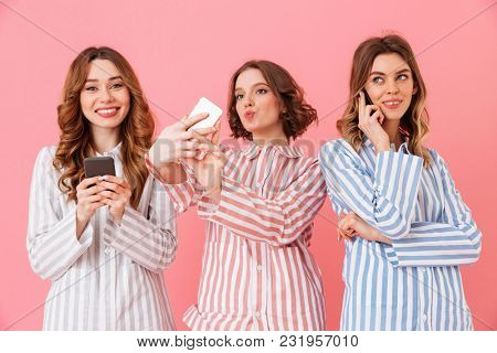 Photo of three gorgeous young girls 20s wearing colorful striped pyjamas communicating and using smartphones during happy sleepover isolated over pink background