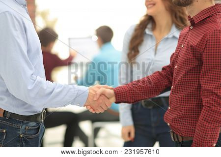 Business people handshake in modern office.
