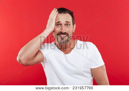 Image of confused scared adult man standing isolated over red background looking camera.