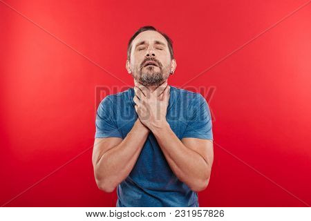 Portrait of adult bearded man 30s having painful sore throat and touching neck with both hands isolated over red background