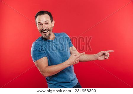 Handsome bearded man 30s in casual blue t-shirt pointing fingers aside on copyspace isolated over red background