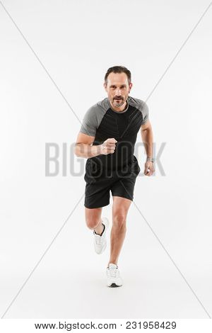 Full lenght portrait of handsome serious mature sportsman running isolated over white background wall. Looking camera.