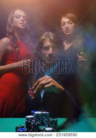 fortunate gambler surrounded by seductive elegant women