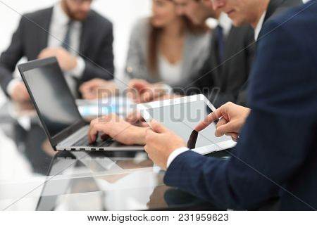 Business man using a tablet  while business people talking in th