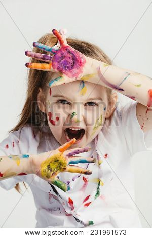 Little girl making funny faces. Funny kid. Colorful body makeup.