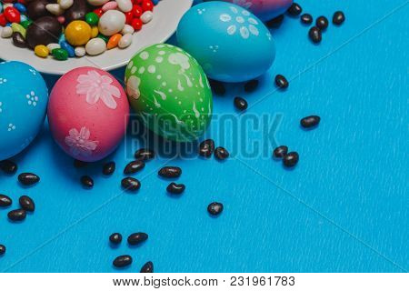 Colored Easter Eggs On A Saucer On A Blue Background. Happy Easter.