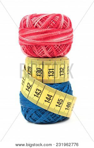 Blue And Red Sewing Thread With Yellow Measuring Tape On A White Background
