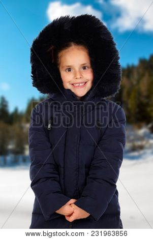 Sheltered girl with black coat and hood in a cold and snowed day