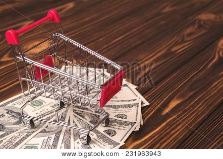Empty Shopping Trolley On A Pile Of Dollars On A Wooden Background.
