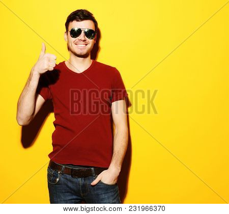 Portrait of a cheerful young man showing okay