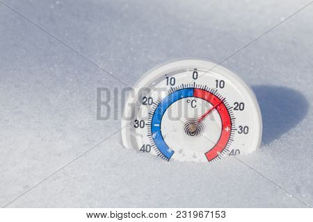 Thermometer with celsius scale in melting snow showing plus 15 degree temperature hot spring weather or global warming concept