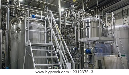 Stainless Steel Brewing Equipment : Large Reservoirs Or Tanks And Pipes In Modern Beer Factory. Brew