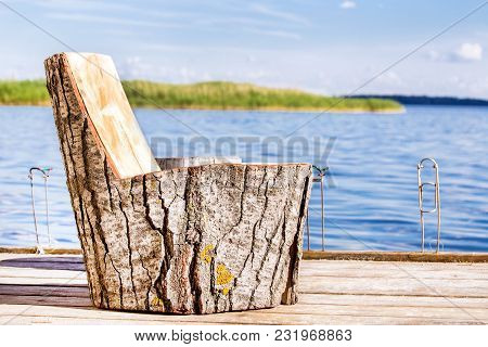 Wooden Chair Made Of Big Stump On A Fishing Pier On Lake Or River.