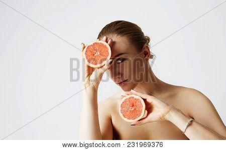 Portrait Of Comic Happy Girl Holding Halves Of Orange Near Face