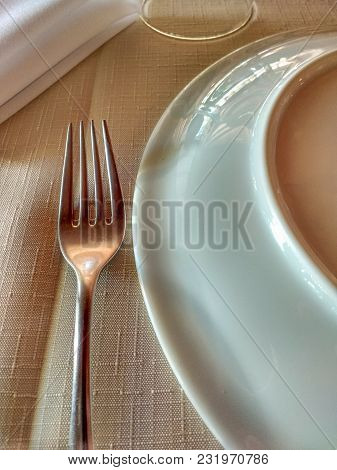 Fork, Plate And Napkin On Tidy Linen Towel To Start Dinner, With Soft Light.