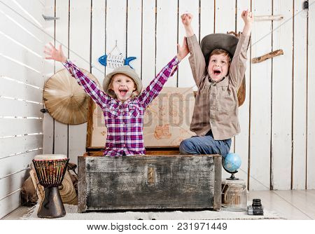 two little laughing children with hands up sitting in big old chest