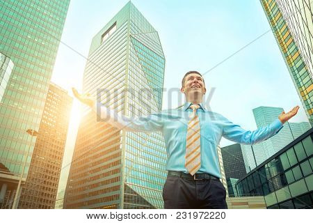 Businessman. Happiness businessman with phone around skyscrapers in La Defence district in Paris City with sky background.