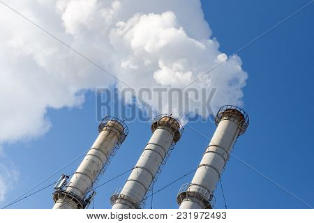 Smoking Pipes Making Clouds Against Blue Sky Background. Dioxide Air Contamination. Environmental Po