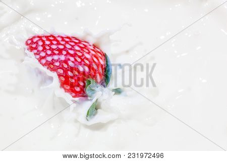 Strawberry Falling In A Bowl Of Milk With Milk Splashing