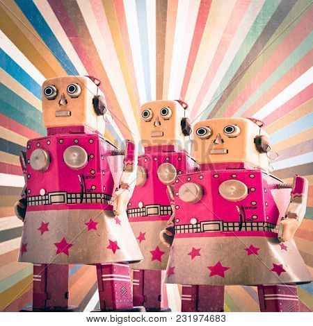 three girl robot toys looking forward, toned image