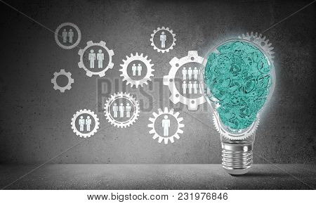 Lightbulb With Multiple Gears Inside Placed Against Social Gear Structure On Grey Wall. 3d Rendering