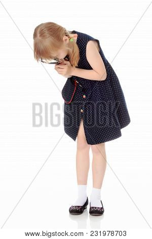 A Nice Little Girl Looks Through A Magnifying Glass. The Concept Of A Happy Childhood, Science And E
