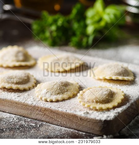 Uncooked Tortelli With Cheese Filling On A Wooden Board.