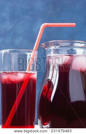 Healthy Refreshing Drink From Ice Hibiscus Tea And Red Berries And Fruits In Pitcher And Tall Glass