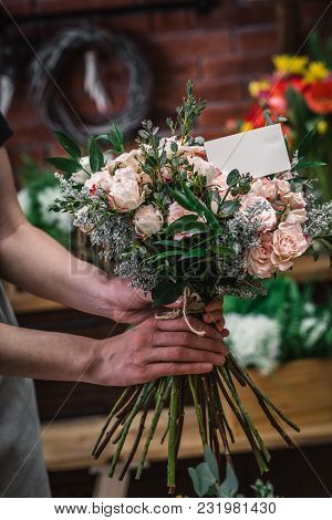 Florist Making Beautiful Bouquet At Flower Shop