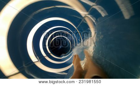 Person Going Down A Blue Water Slide With White Rings And Into A Tube At A Water Park Aqua Park. Sum