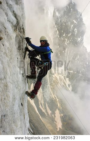 Climber With An Ice Ax Climbs On A Vertical Ice Wall. He Is Wearing Equipment. Helmet, Rope, Crampon