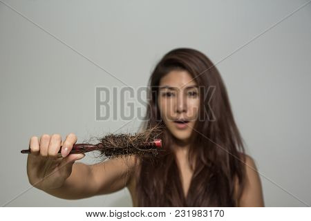 Young Girl Holding Comb With Hair Fall Feeling Shocked. Lady Hair Problem Holding Loss Hair Comb In