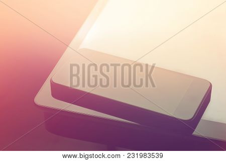 Close-up Of Mobile Phone And Tablet Lying Above Table With Yellow Light Background.
