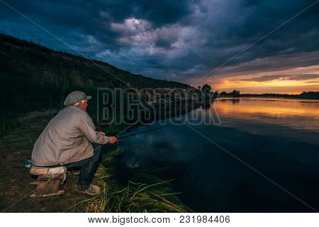 Grandpa The Fisherman Sits By The River With A Fishing Pole Against The Backdrop Of A Beautiful Suns